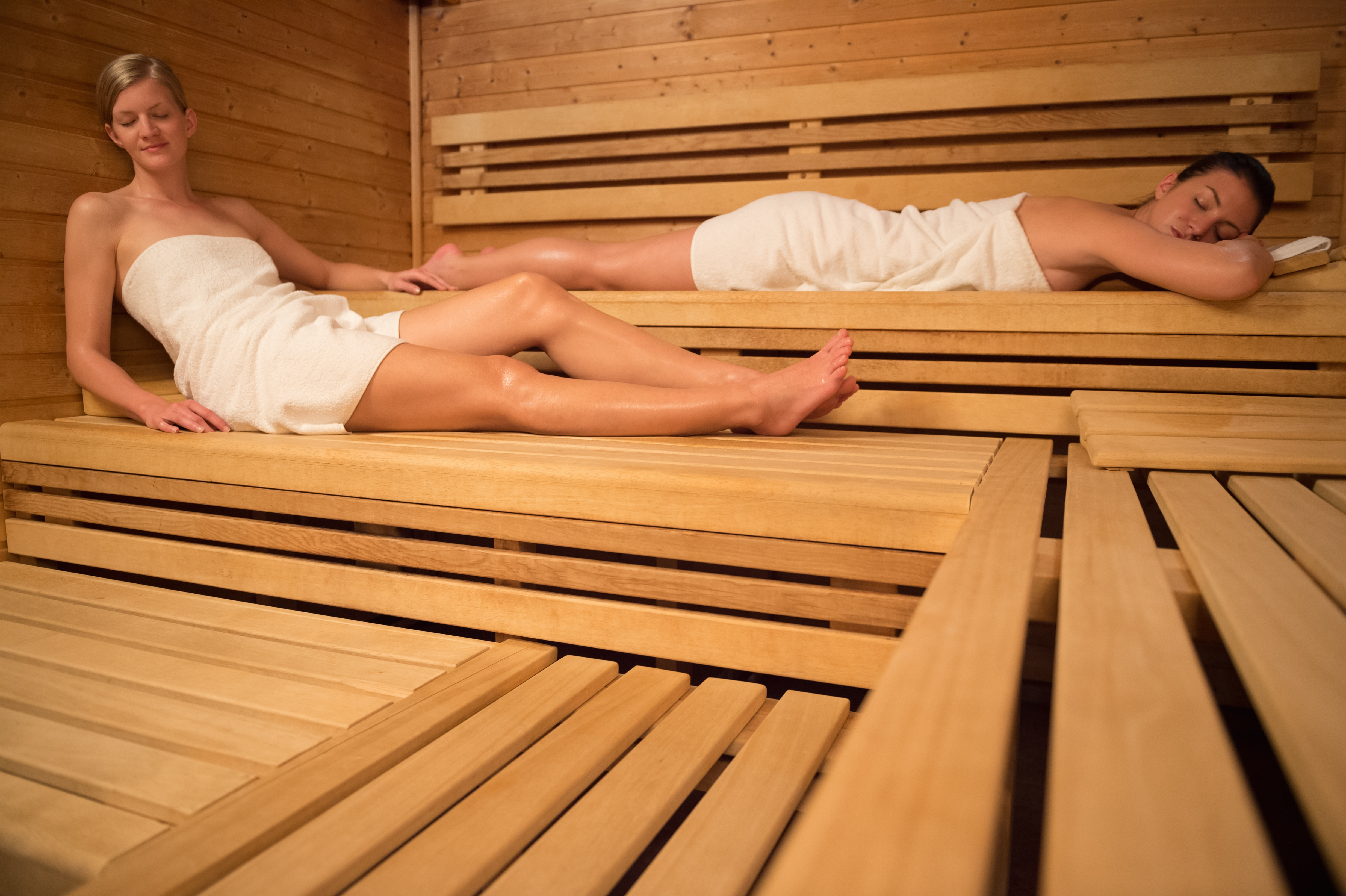 Two women relaxing on wooden benches in sauna. Trying a Nordic Spa in Québec City offers the chance to experience a choice of thermotherapies.
