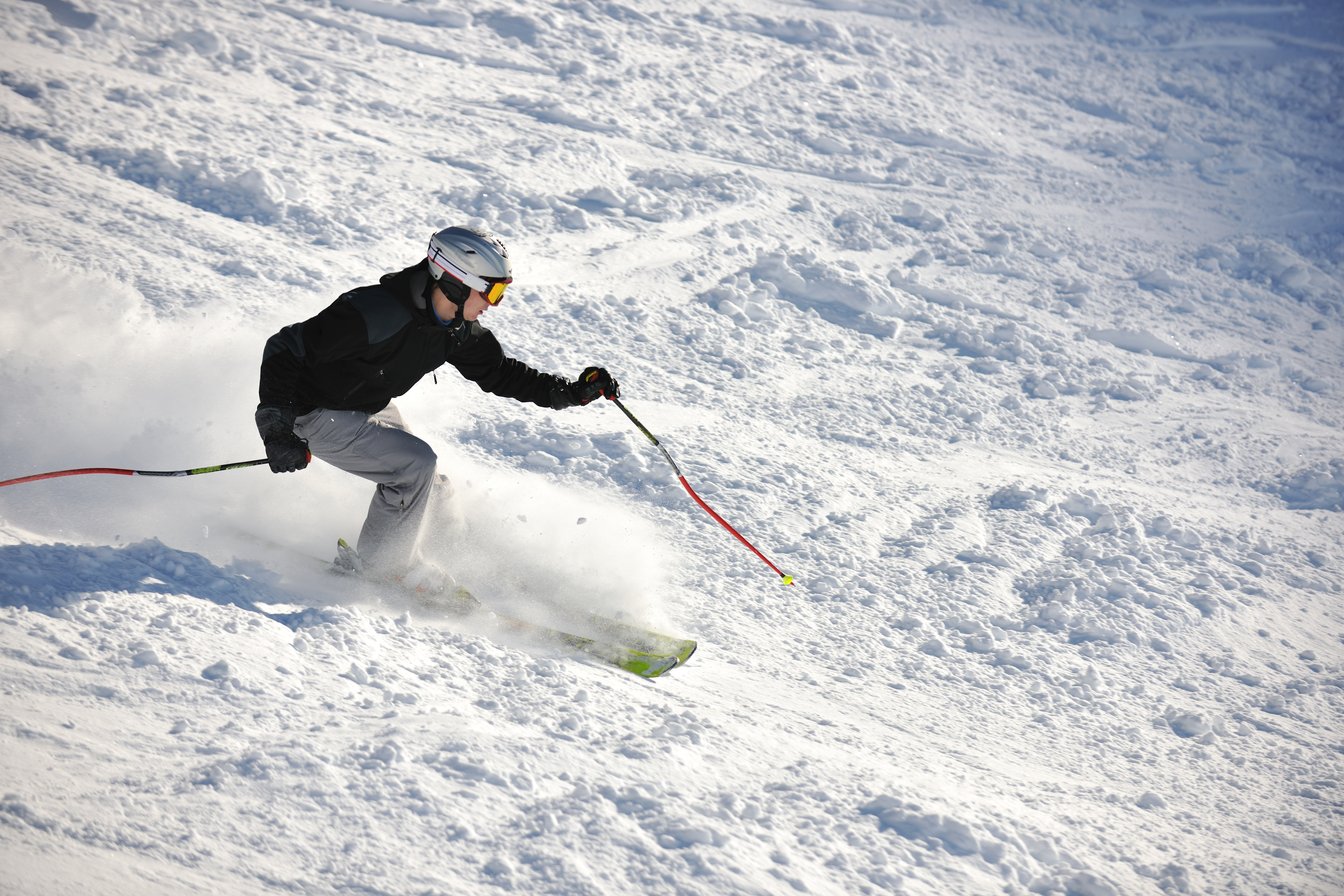 Tackle the ski slopes at four Québec City Resorts. This man is heading downhill on skis.