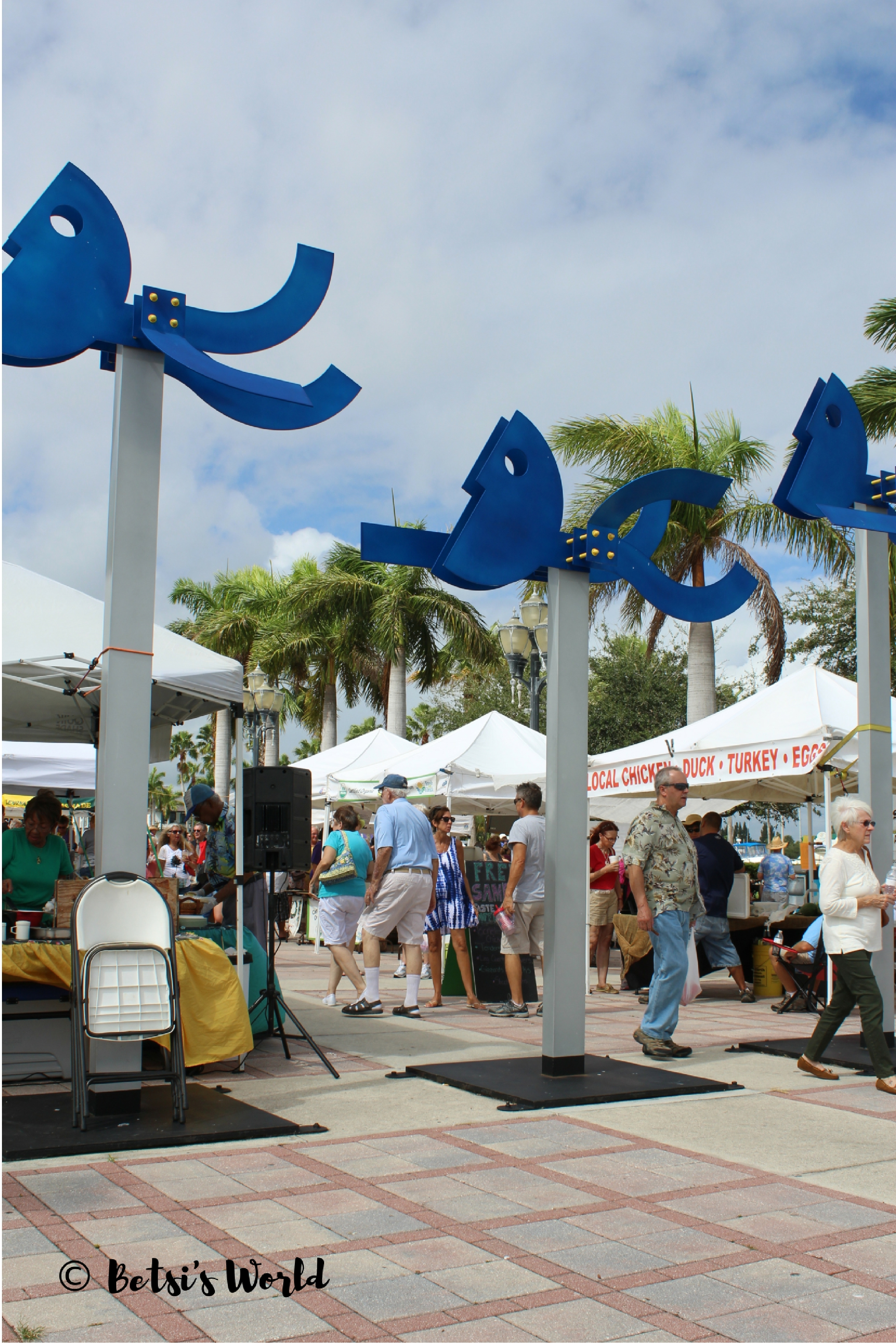 Fort Pierce Farmers' Market with artistic sculpture and produces stands selling meats and fruit.
