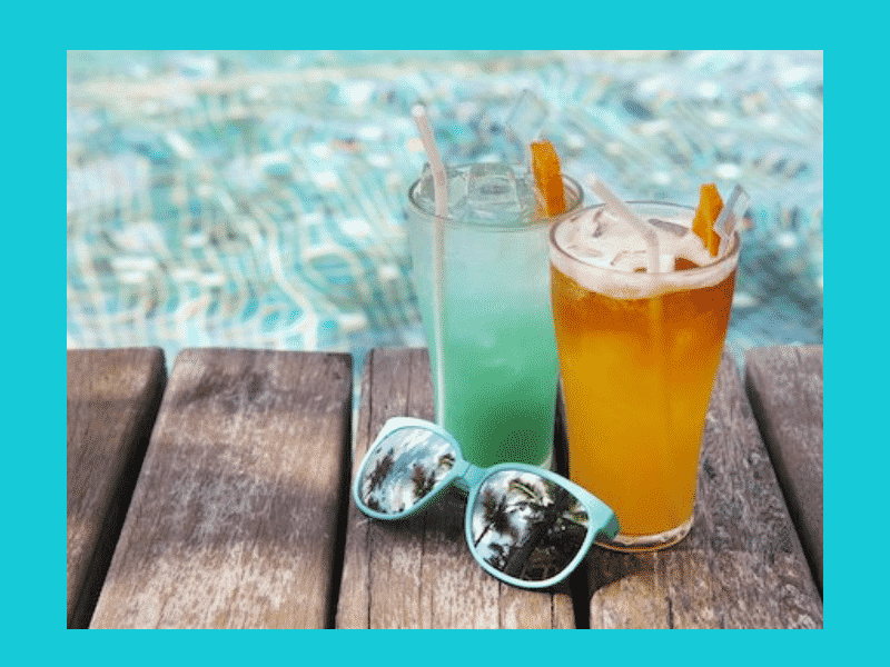 turquoise water with 2 cocktails and teal sunglasses on a wood planks