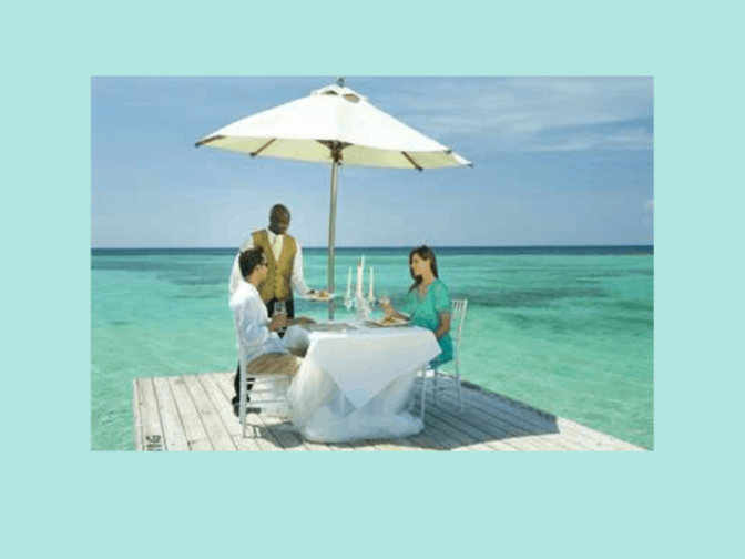 turquoise water, white umbrella, table with white cloth, two people seated at table with waiter wearing gold vest and black pants