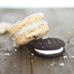 Oreo macaroon and an oreo cookie on a wood plank table with crumbs