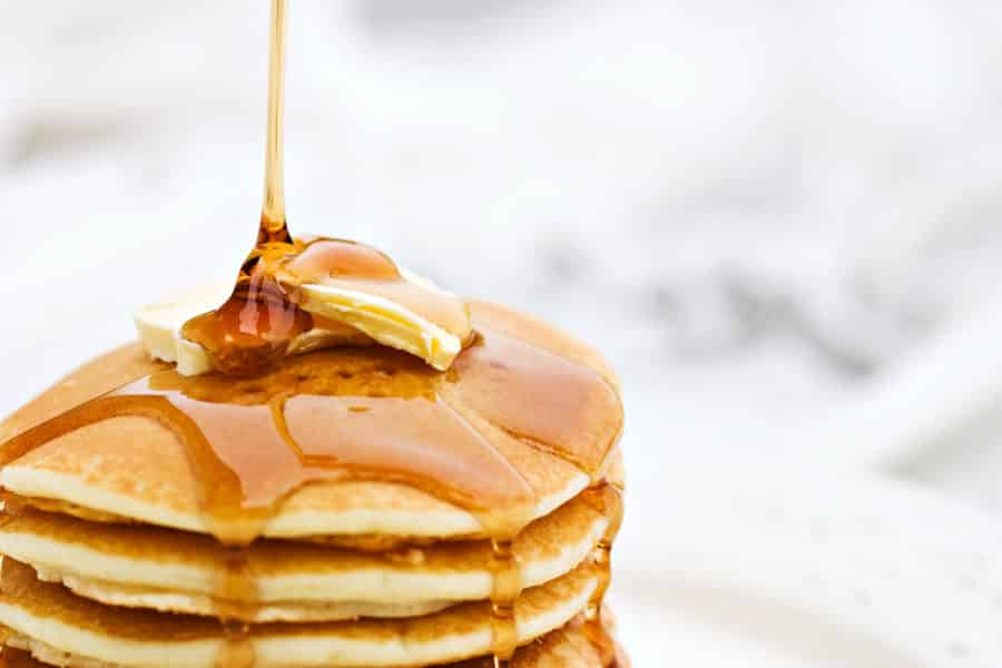 Stack of pancakes with butter and dripping with syrup