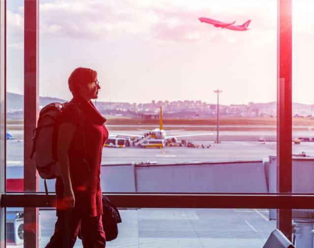 Woman with Hand Luggage Backpack in casual Clothing walking along large Window of Airport Terminal while Air Plane taking off behind