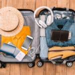 Open suitcase with orange top, hat, electronic chargers, money and jeans
