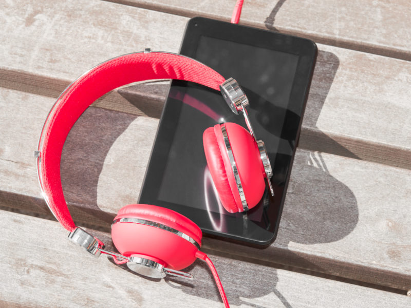 Red colored headphones and tablet PC