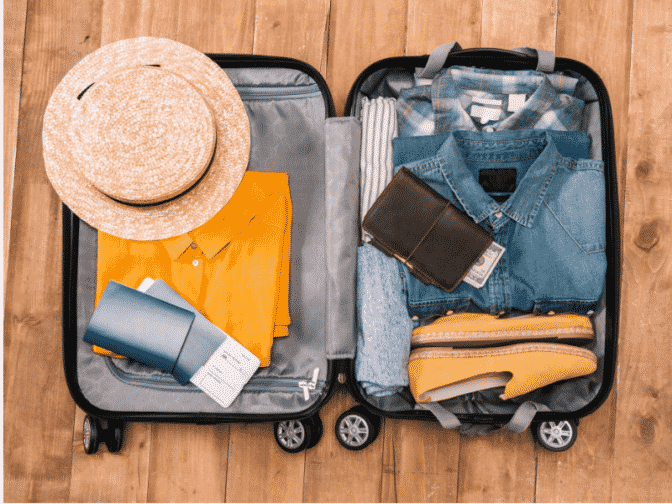 Open suitcase with hat, travel documents, yellow shirt, and electronic charger
