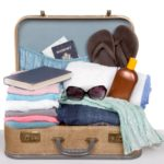 Open tan suitcase with clothes, book, passport, sunglasses, electronics and hat