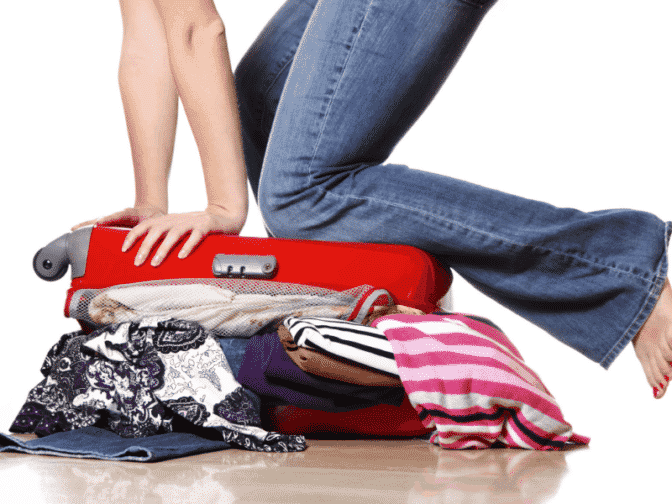Red suitcase, filled to overflowing, girl kneeling on top, trying to close