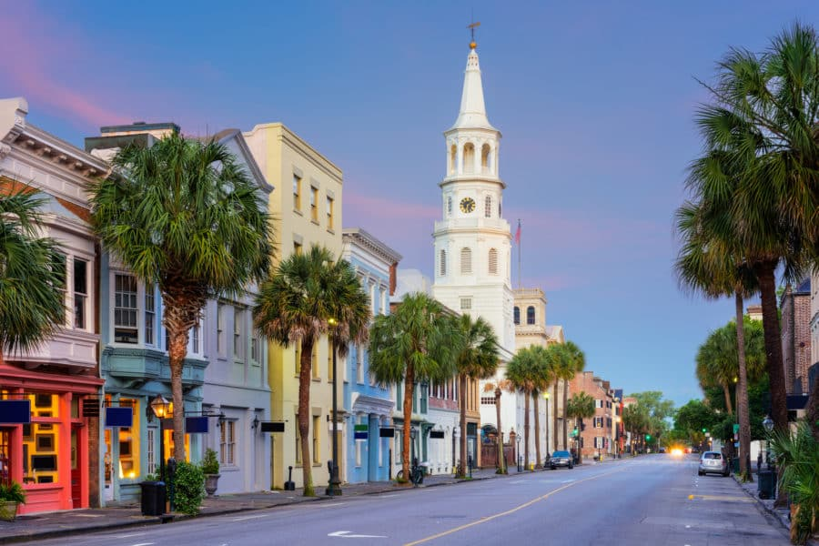 Charleston, South Carolina, USA in the French Quarter at dusk. A church's tall spirit, and buildings line the street