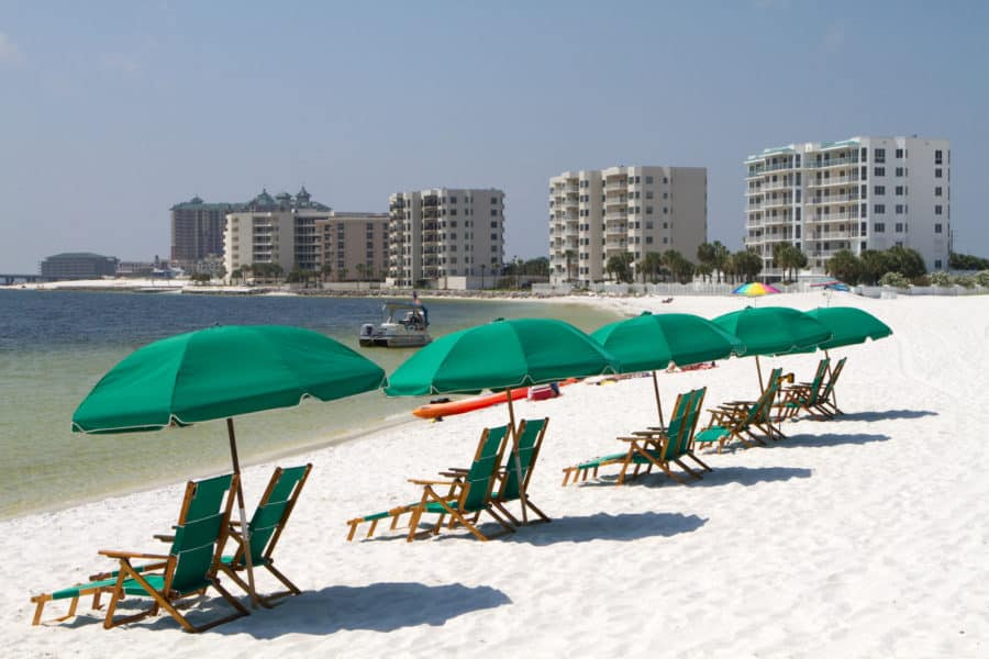 Tourists relax laying on the beach behind beach umbrellas and beach chairs with highrise condominiums in the background.