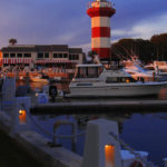 red and white lighthouse at Hilton Head, South Carolina. dusk. hotel and marina