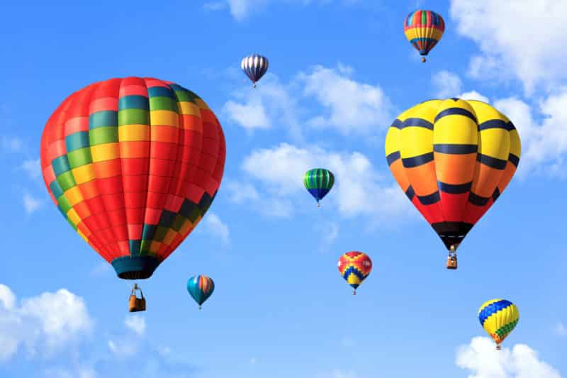 colorful hot air ballon in a cloud filled blue sky