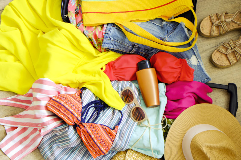 Open suitcase with pile of unfolded clothing on the floor. Woman packing for tropical vacation concept. Multiple unpacked female clothing items prepared for travel. Background, close up, copy space.