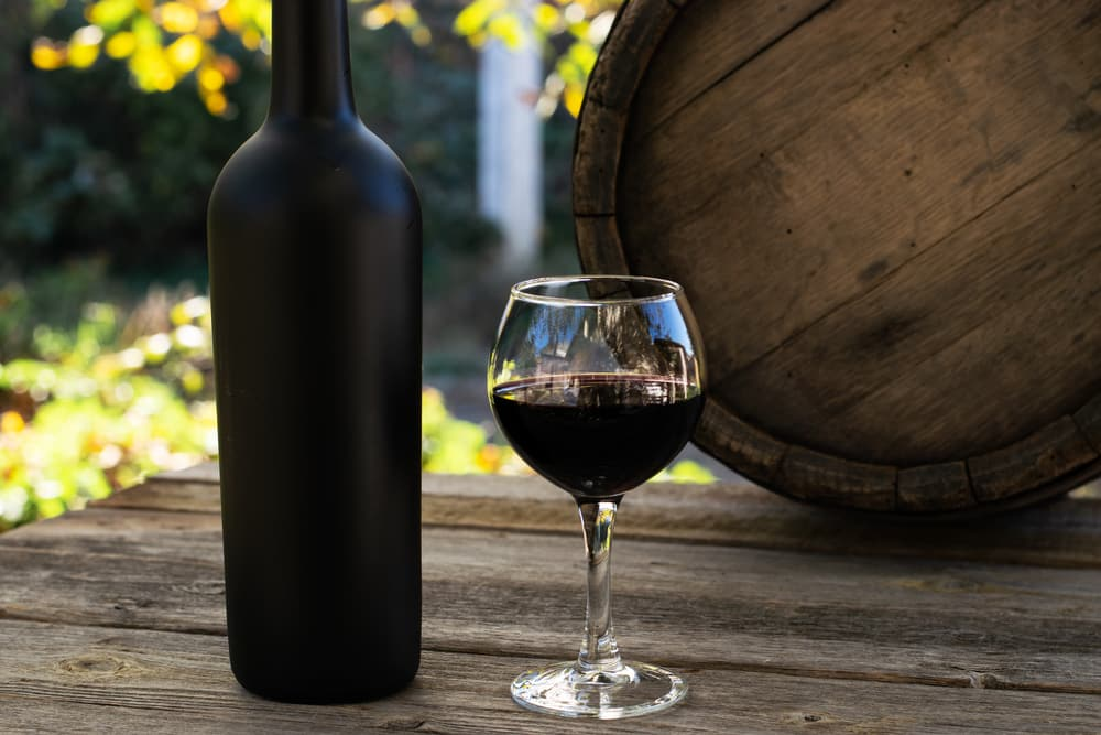 a wine bottle, a wine glass full of red wine, outside on a wooden table with a wooden cask as an example of an activity you can do on your romantic getaway to a vineyard in the south