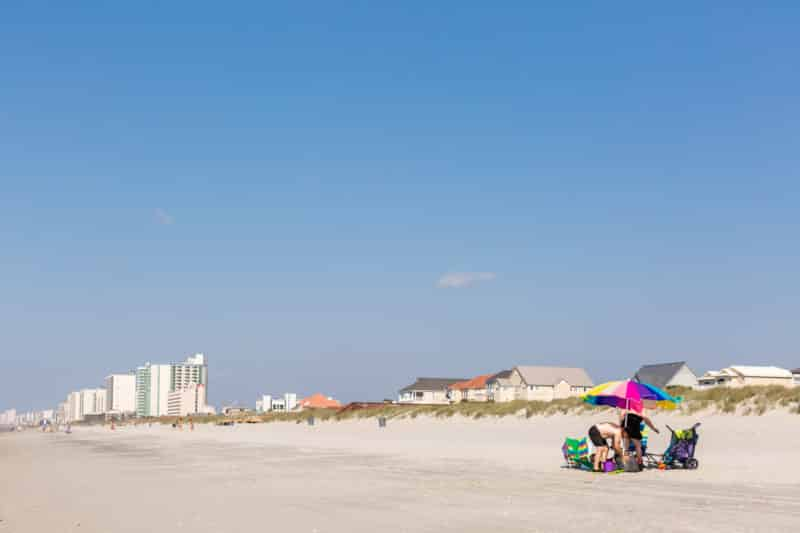 family on beach under striped umbrella, beach houses and hotels on dunes