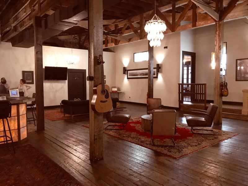 Large room with wooden floors, guitars on the walls and comfortable chestnut leather chairs
