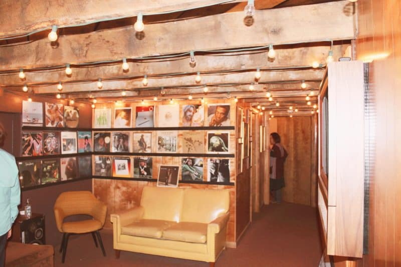 tan sofas, records lining the wall, wood paneled room