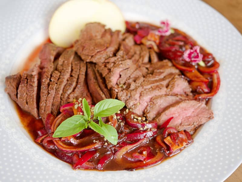 kangaroo meat on white plate with raspberry sauce
