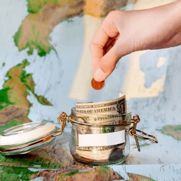 money jar with coins laying on world map