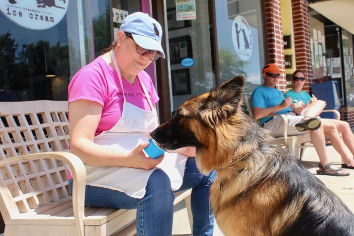 dog eating ice cream from cup in front of shop with woman in apron, pink shirt and jeans feeding the dog ice cream