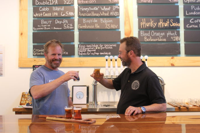 2 men toasting with beer behind counter with beer choices on chalkboard behind them and taps on the counter