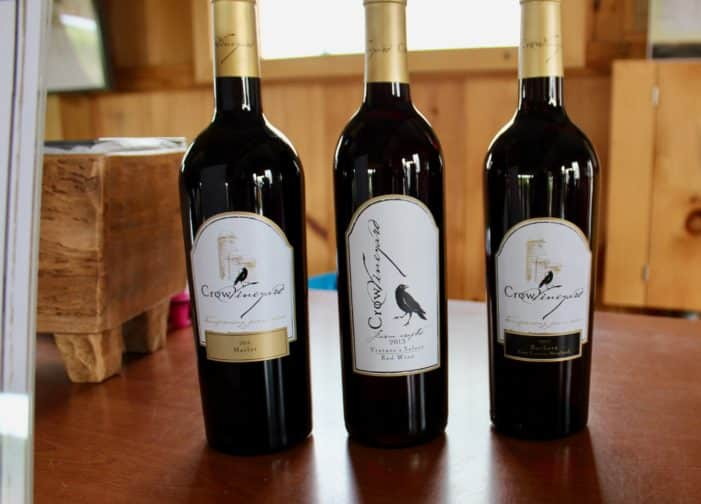 3 bottles of Crow Vineyards wine on wood table with window in background