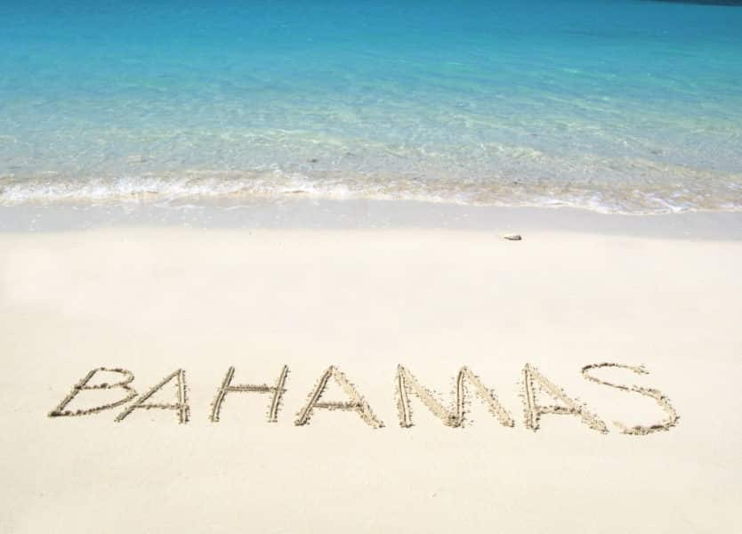 Bahamas written on white sand beach with turquoise water