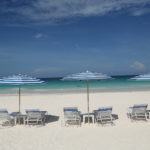 white sand beach with lounges and umbrellas