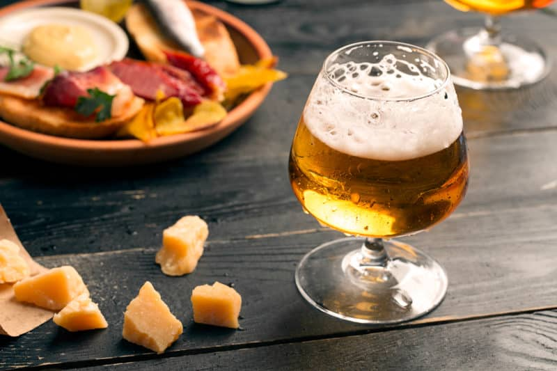 Two glasses of beer on black table with snacks