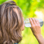 blonde haired woman drinking out of a water bottle