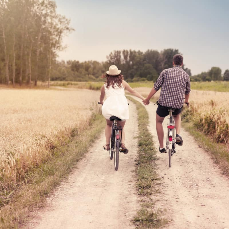 a couple biking in a field and holding hands, an activity to do during your budget-friendly romantic getaway