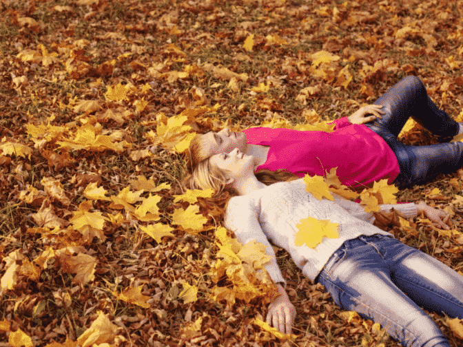 couple laying in fall leaves multicolored