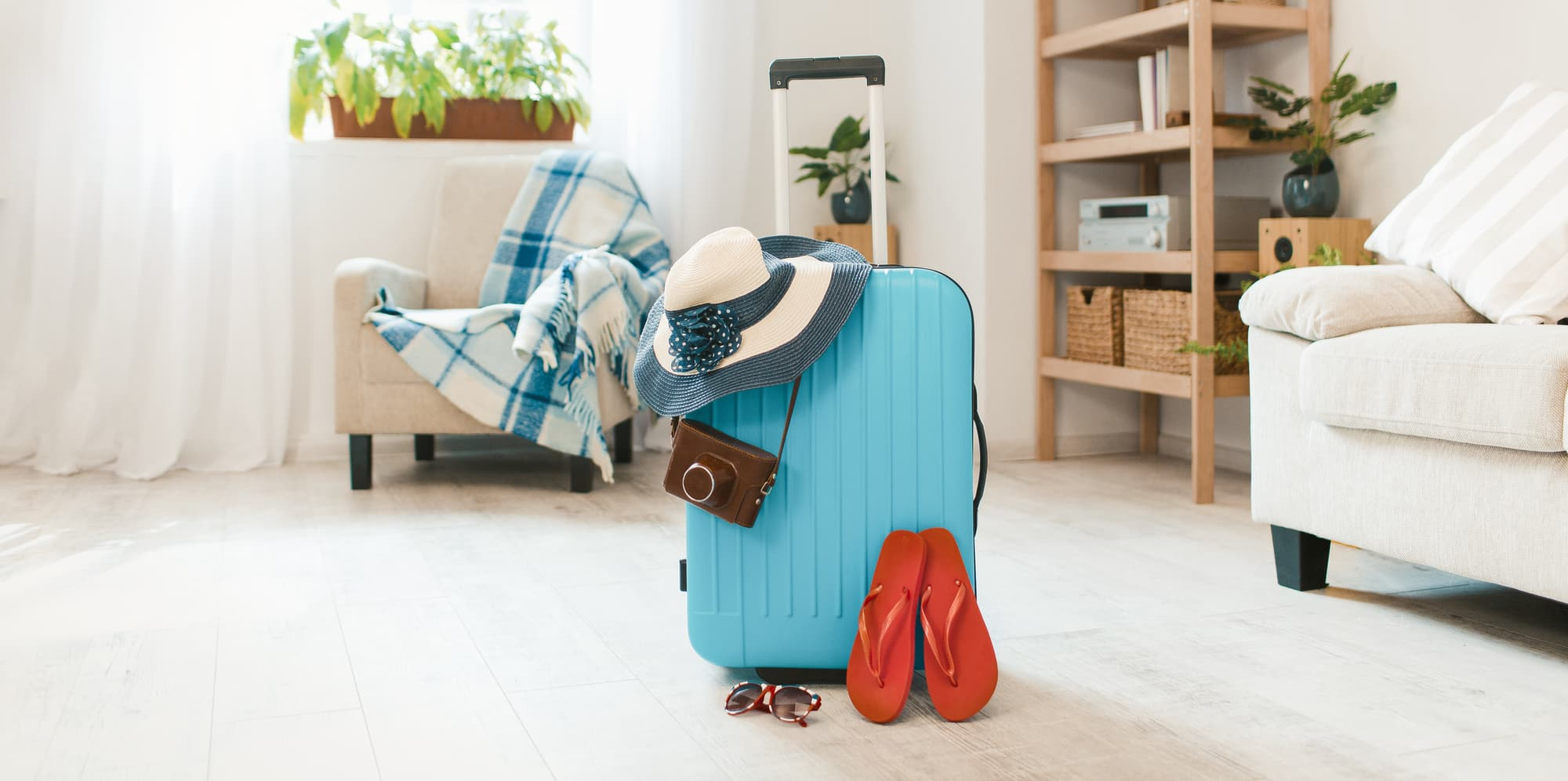 Blue suitcase with havaianas and hat at home interior.