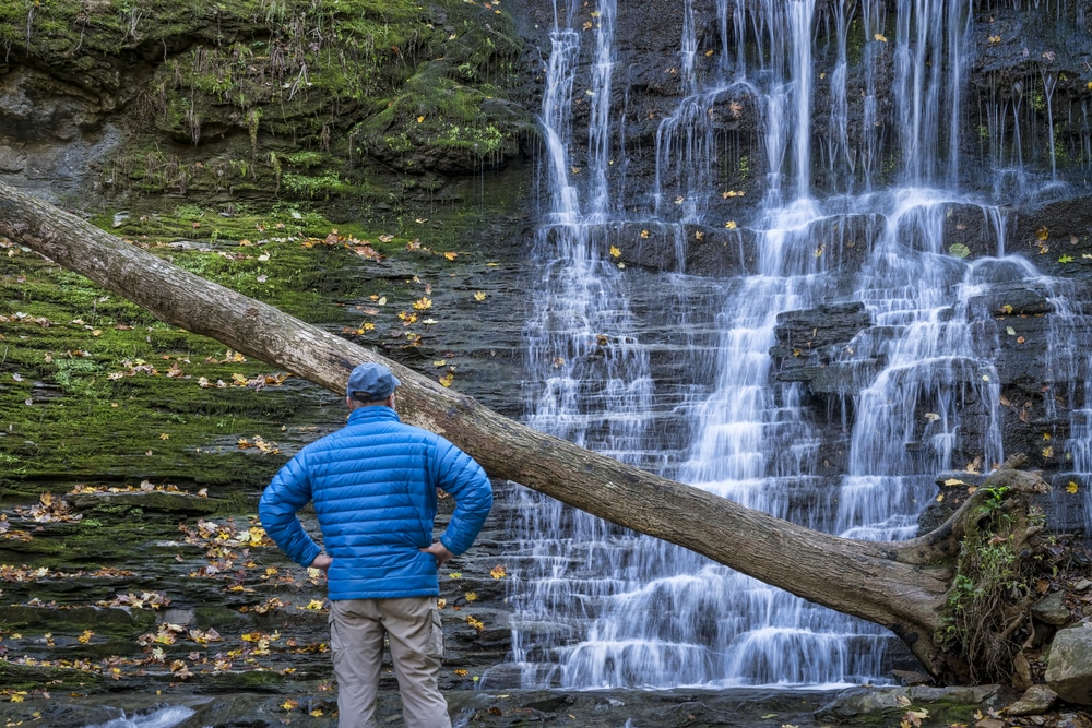 Jackson Falls at Natchez Trace Parkway with a man standing in front looking at the waterfall. A romantic getaway for couples