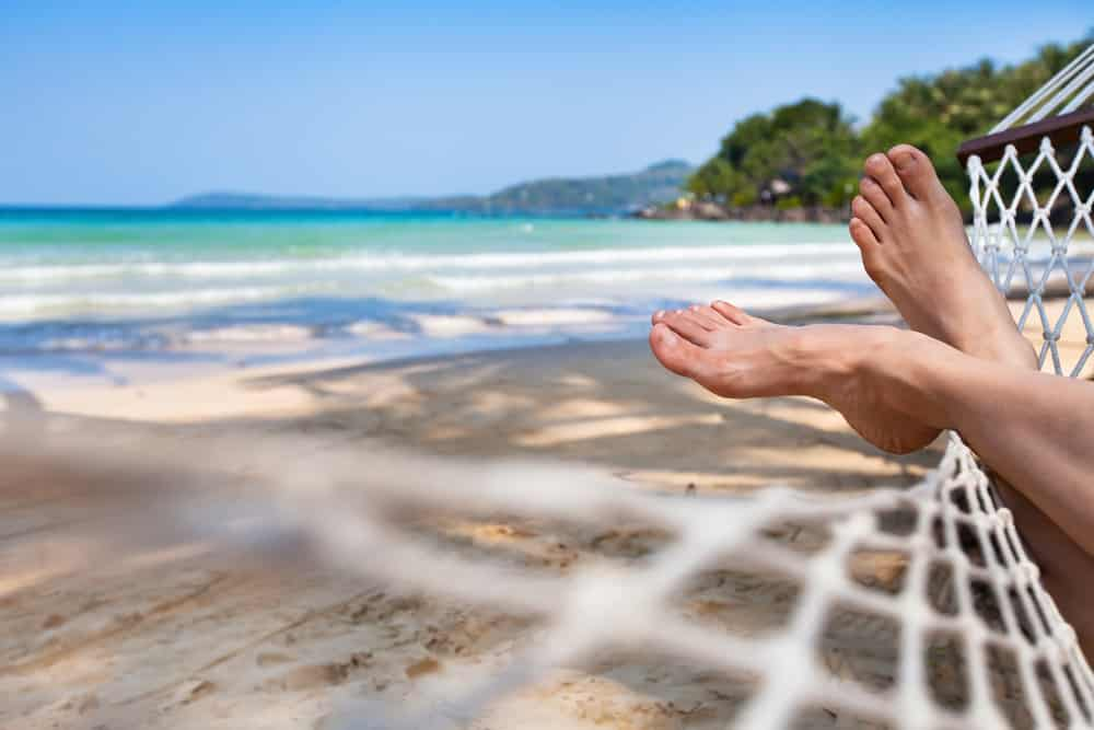 someone relaxing on a hammock with a view of their feet on a southern beach with blue skies and blue water. A perfect place to relax on a southern vacation