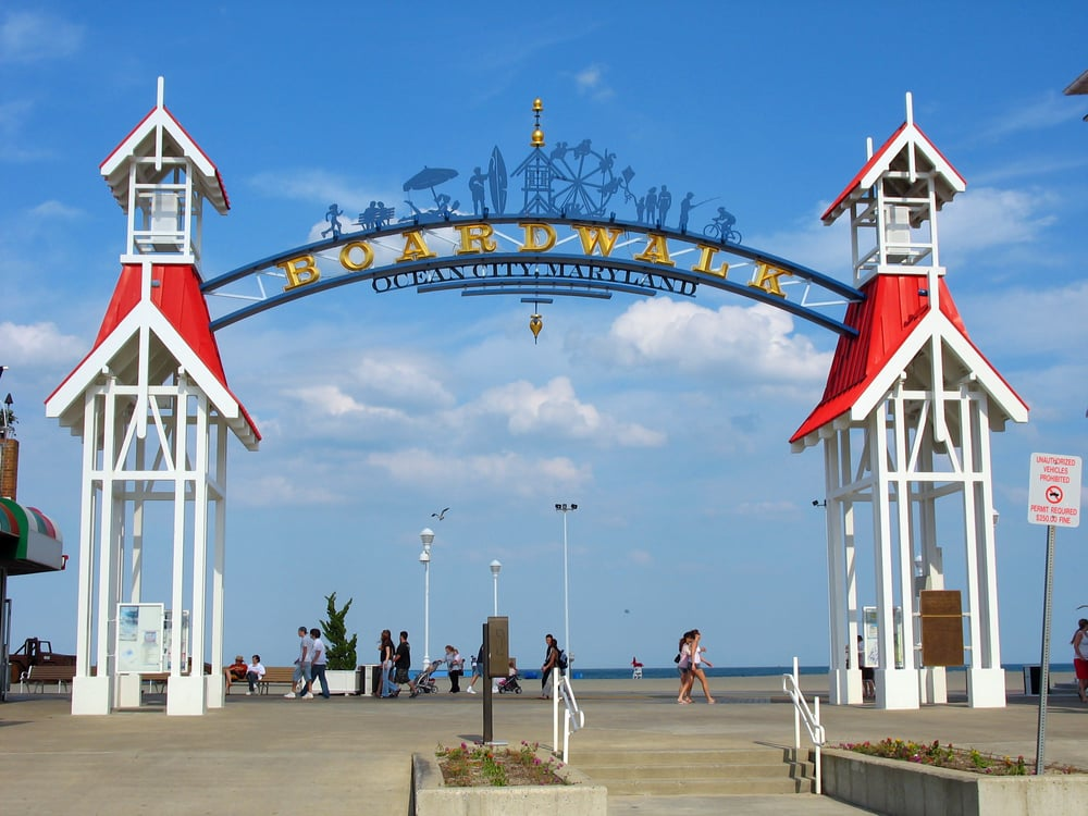 the boardwalk in ocean city, maryland with blue skies and blue water. A great place to walk with your partner in the south on your vacation
