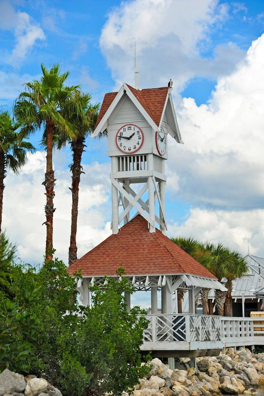 View of a historic beach pier with palm trees, a clock and blue skies, a great for spending some quality time together on your Anna Maria Island Romantic Getaway!