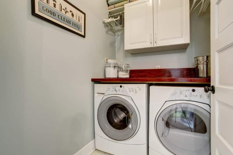 Small laudnry room with tile floor, door, and washer dryer set.