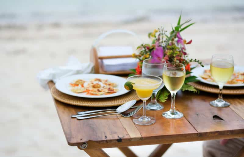 a wooden table on the beach with dinner and a glass of wine