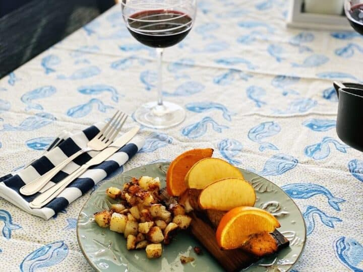 blue print table cloth with grilled citrus salmon and wine glass filled with red wine