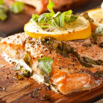 salmon on plank topped with lemon slices