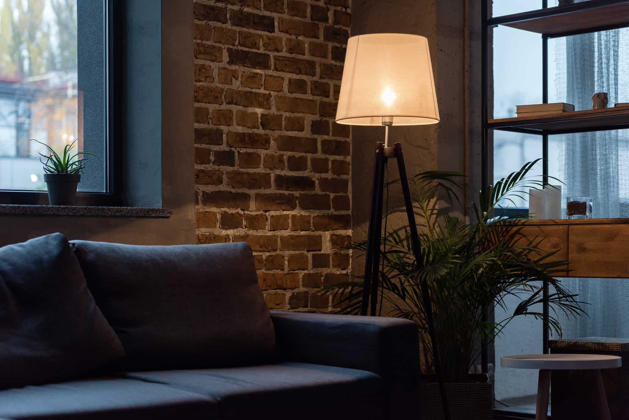 sofa against a brick wall with a light
