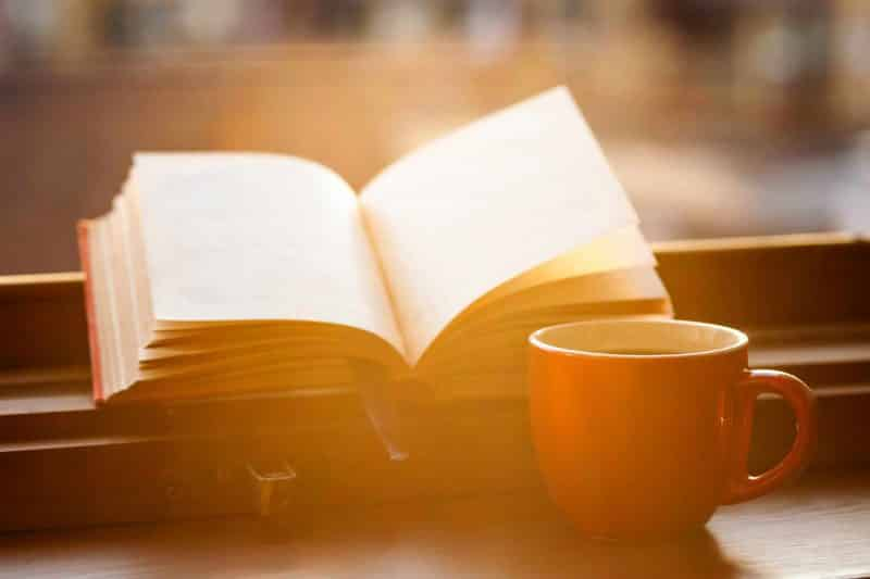 book with cup of coffee on a windowsill