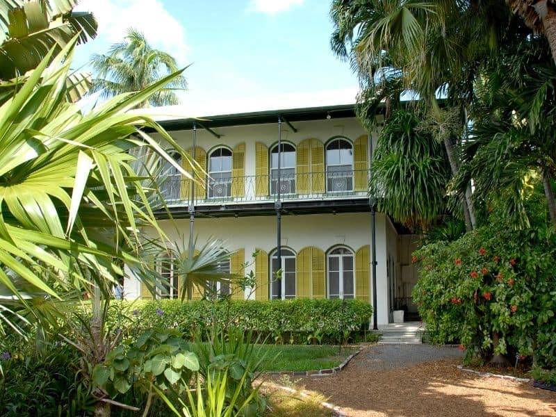 Ernest Hemingway's house in Key West. Yellow two story with expansive window and tropical greenery surrounding the house