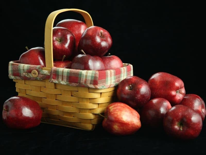 red apples spilling out of a rustic basket on a black background