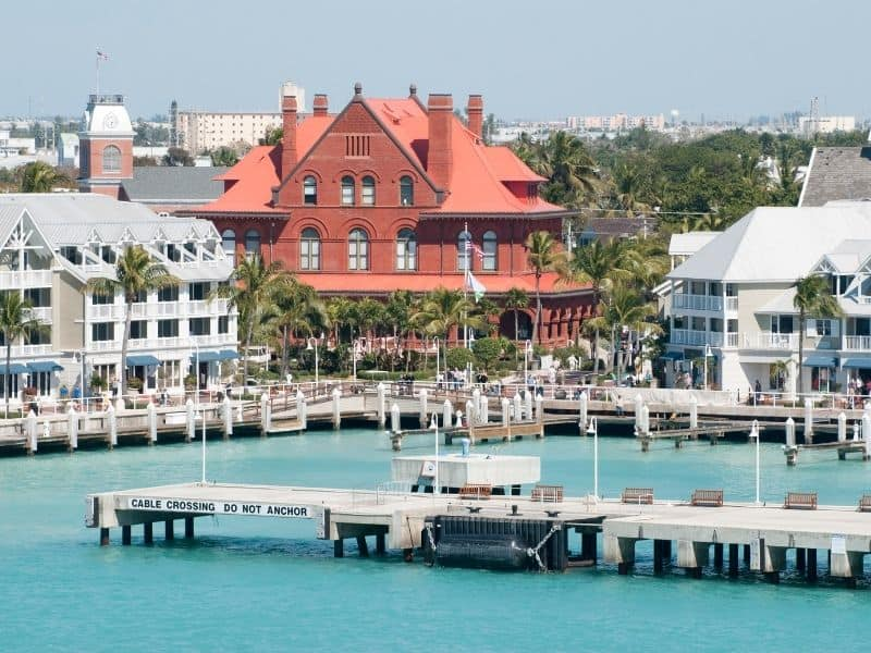 Key West downtown buildings in pink, red, and green, turquoise water of the harbor