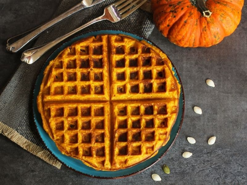 a pumpkin waffle on a teal plate, with a grey background and an orange pumpkin behind it with a silver fork and spoon and pumpkin seeds scattered around the plate, an example of a pumpkin, healthy recipes