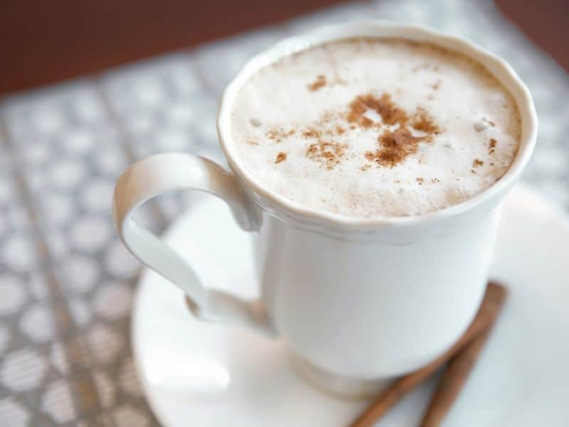 a pumpkin spice latte in a white mug with cinnamon sticks on a white placemat, an example of pumpkin healthy recipes