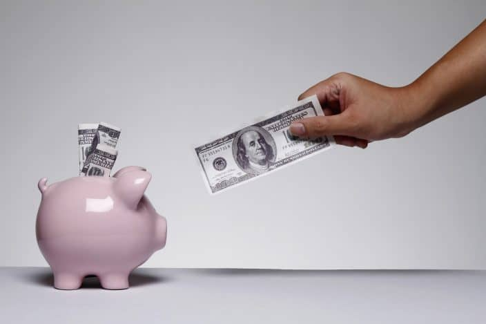pink piggy bank with cash and hand with dollar bill reaching toward piggy bank